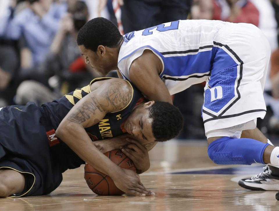 Maryland's Nick Faust, left, and Duke's Quinn Cook wrestle for control of a loose ball during the first half of an NCAA college basketball game at the Atlantic Coast Conference men's tournament in Greensboro, N.C., Friday, March 15, 2013. (AP Photo/Bob Leverone)