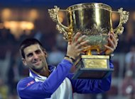 Novak Djokovic of Serbia poses with the trophy after beating Jo-Wilfried Tsonga of France in the men's singles final at the China Open tennis tournament in Beijing on October 7, 2012. Djokovic beat Tsonga 7-6, 6-2 to win the China Open for a third time