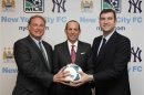 Handout photo of New York Yankees President Randy Levine, Major League Soccer Commissioner Don Garber, and CEO of Manchester City FC Ferran Soriano smiling during a press announcement in New York