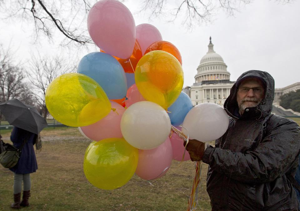 Bruce Lundeen of Harrisonburg, Va., holds balloons to hand out to fellow Occupy Congress protesters who plan a day of demonstrations and activities on Capitol Hill in Washington, Tuesday, Jan. 17, 2012.  (AP Photo/J. Scott Applewhite)