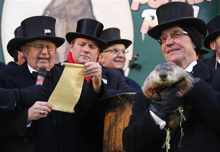 Groundhog co-handler Ron Ploucha (R) holds Punxsutawney Phil as the Groundhog Club&#39;s Bob Roberts (L) reads the famous groundhog&#39;s annual weather prediction on Gobbler&#39;s Knob in Punxsutawney, Pennsylvania, on the 127th Groundhog Day, February 2, 2013. REUTERS/Jason Cohn