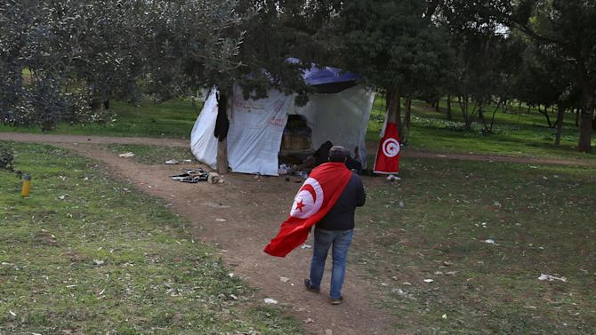 An unemployed Tunisian walks near a tent during a protest at el-Mourouj park in Tunis