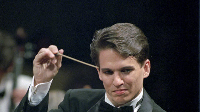 FILE - In this May 1995 file photo, Boston Pops Orchestra conductor Keith Lockhart wields the baton during a performance at Symphony Hall in Boston. Lockhart was just 35 when he took over as the Pops conductor in 1995. In 20 seasons, he has raised his baton 1,700 times and has shared the stage with guest artists as diverse as Aerosmith, Robert DeNiro and Big Bird. (AP Photo/Julia Malakie, File)