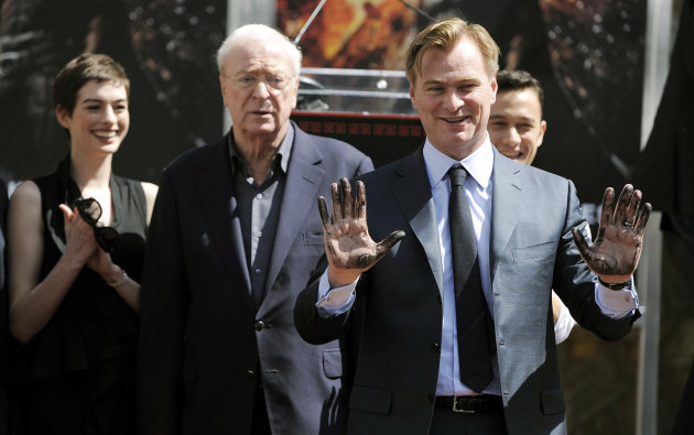 Christopher Nolan, director of the upcoming film &quot;The Dark Knight Rises,&quot; holds up his hands after putting them in cement during a ceremony for him at Grauman&#39;s Chinese Theatre on Saturday, July 7, 2012, in Los Angeles. Looking on from left are cast members Anne Hathaway, Michael Caine and Joseph Gordon-Levitt. (Photo by Chris Pizzello/Invision/AP)