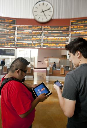In this June 15, 2011 photo, moviegoers Luis Garcia, 37, left, and Elias Sanchez 26, watch movie trailers on Flixster on their iPad and iPhone, before buying their tickets at the ArcLight Hollywood cinema in Los Angeles. Theater owners have tried a variety of methods to get folks to keep quiet and stay off their phones during shows, from playing amusing messages beforehand to having ushers sweep through the auditorium during the show, said John Fithian, president of the National Association of Theatre Owners. (AP Photo/Damian Dovarganes)