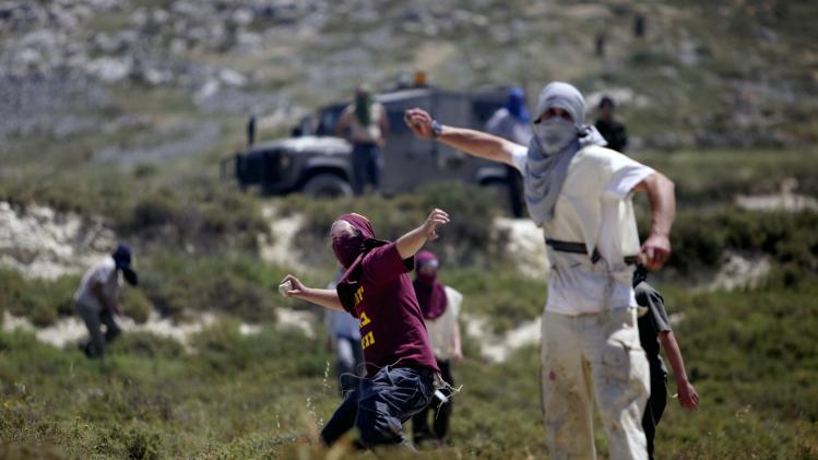 Jewish settlers throws rocks towards Palestinians, not pictured, during clashes near the Jewish settlement of Yitzhar, near Nablus, Tuesday, April 30, 2013. In the West Bank, a Palestinian man fatally stabbed an Israeli waiting at a bus stop and fired on police before he was detained by Israeli security forces, officials said. The Israeli military said that following the stabbing settlers began rioting, hurling rocks at Palestinian vehicles and setting fire to nearby fields. It said two rioters were arrested. (AP Photo/Nasser Ishtayeh)