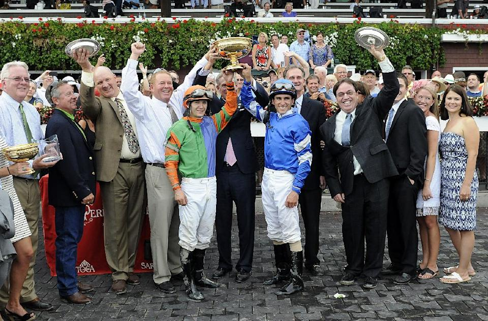 Jockeys David Cohen, center left, and Ramon Dominguez, celebrate with horses' owners and trainers they rode Golden Ticket and Alpha, respectively, to a dead heat in the Travers Stakes horse race at Saratoga Race Course in Saratoga Springs, N.Y., Saturday, Aug. 25, 2012. (AP Photo/Hans Pennink)