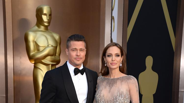 FILE - In this Sunday, March 2, 2014, file photo, Brad Pitt, left, and Angelina Jolie arrive at the Oscars at the Dolby Theatre in Los Angeles. Jolie and Pitt were married Saturday, Aug. 23, 2014, in France, according to a spokesman for the couple. (Photo by Jordan Strauss/Invision/AP, File)