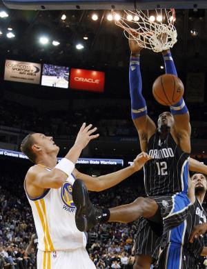 Orlando Magic's Dwight Howard (12) dunks in front of Golden State Warriors' Andris Biedrins (15), of Latvia, during the first half of an NBA basketball game in Oakland, Calif., Thursday, Jan. 12, 2012. (AP Photo/Marcio Jose Sanchez)