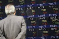"A man looks at an electronic shares index board in front of a securities company in Tokyo, 2008. Asian markets rallied and the euro held on to strong gains from New York after the European Central Bank chief said it would do ""whatever it takes"" to save the under-pressure single currency"