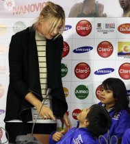 Russia's Maria Sharapova talks with children after a news conference in Bogota December 5, 2013. Sharapova and Serbia's Ana Ivanovic will play in an exhibition match on December 6. REUTERS/John Vizcaino (COLOMBIA - Tags: SPORT TENNIS)