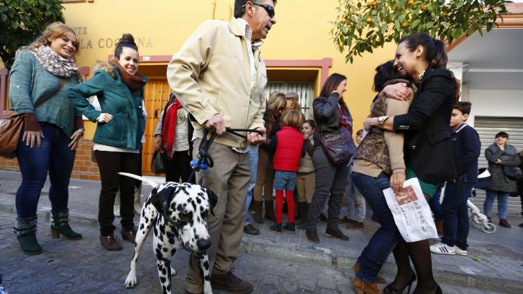 "Winners embrace as they hold a photocopy of the winning ticket to the first prize of ""El Gordo"" in Sanlucar la Mayor"