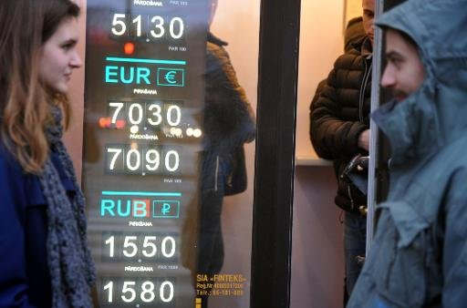 People walk past a currency exchange office in Riga, Latvia on December 27, 2013