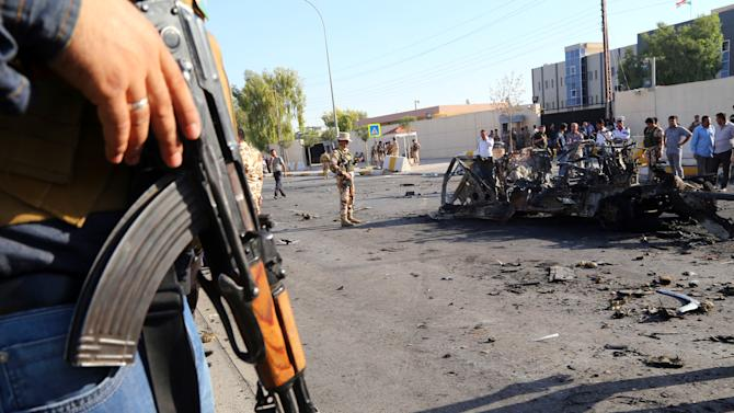 Kurdish security forces and citizens inspect the site of a car bomb attack in front of the main security forces headquarters in Irbil, Iraq, 350 kilometers (217 miles) north of Baghdad, Sunday, Sept. 29, 2013. A twin suicide car bombing and ensuing firefight in the capital of Iraq's largely peaceful self-ruled northern Kurdish region killed and wounded dozens of security forces on Sunday, officials said.(AP Photo)