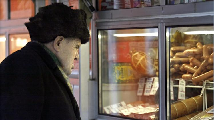An elderly man looks at a meat stall in Moscow on November 26, 2003