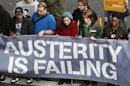 Unemployed youths hold a banner before the start of a protest march in central London