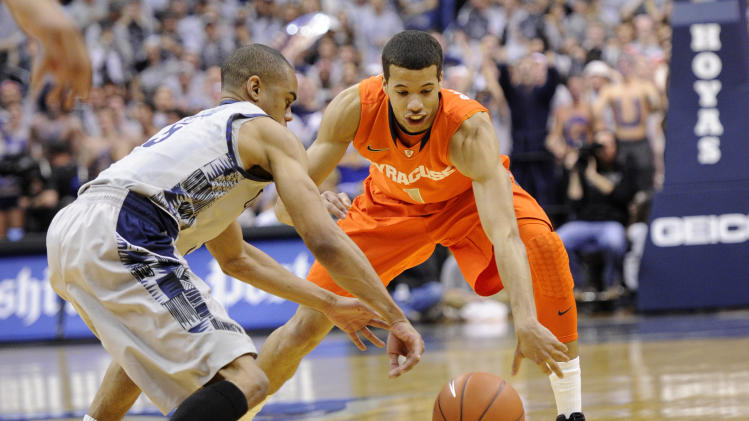 Georgetown guard Markel Starks, left, battles for the ball against Syracuse guard Michael Carter-Williams (1) during the first half of an NCAA college basketball game, Saturday, March 9, 2013, in Washington. (AP Photo/Nick Wass)