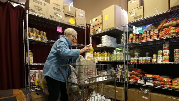 Volunteer Pat Hunziker of Delmar, N.Y., loads food items for a client at the Emmanuel Baptist Church food pantry on Monday, Nov. 19, 2012, in Albany, N.Y. Advocates for the working poor and under-nourished are urging New York's government leaders to raise the minimum wage during a possible special session of the Legislature that could include a salary boost for lawmakers and top government administrators.The groups used their annual Thanksgiving appeal for aid for hungry New Yorkers to push for the wage initiative during a march and rally held in downtown Albany. (AP Photo/Mike Groll)