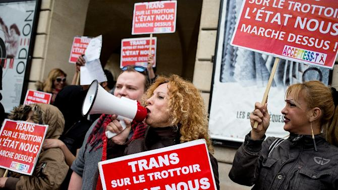 """Sex work union members hold placards reading """"Trans, whore and not whore, state is walking all over us"""" as they protest against a plan to penalise clients of prostitution, on March 30, 2015 in Paris"""