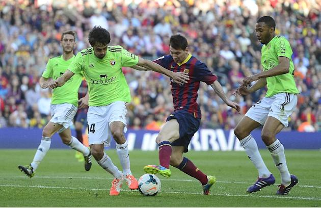 FC Barcelona's Lionel Messi, from Argentina, center, duels for the ball against Osasuna's Alejandro Arribas during a Spanish La Liga soccer match at the Camp Nou stadium in Barcelona, Spain, S
