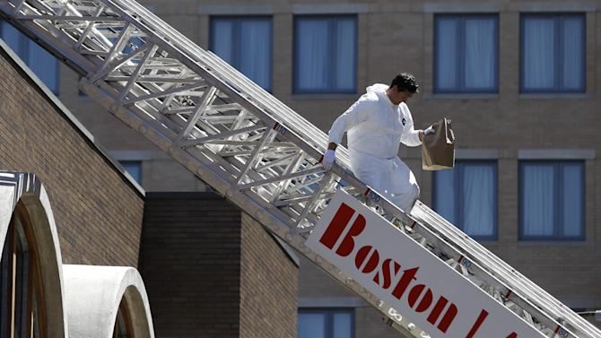 An FBI investigator walks down a fire truck lADDER with a bag from the top of a building at the corner of Boylston Street and Fairfield Street Wednesday April 17, 2013, in Boston. Investigators in white jumpsuits fanned out across the streets, rooftops and awnings around the blast site in search of clues on Wednesday. (AP Photo/Julio Cortez)