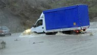 A truck attempts to manoeuvre down a flooded street around Torpe near Nuoro on Sardinia island November 18, 2013. REUTERS/ANSA/Massimo Locci