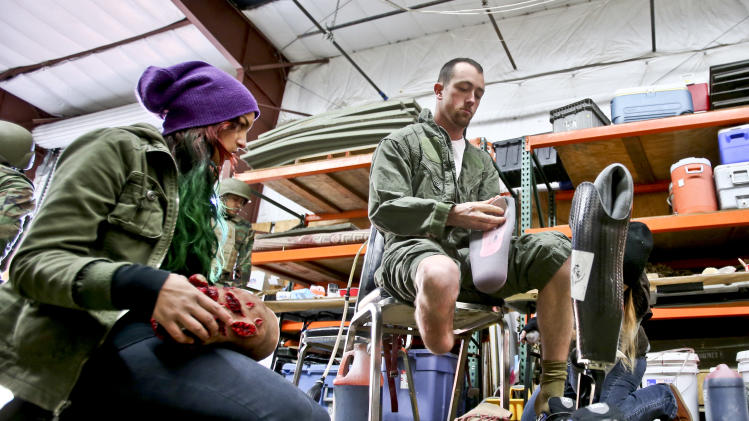 In this  Tuesday Feb. 12, 2013, photo, former Navy corpsman Joel Booth, who lost a leg in Afghanistan,  prepares with the help of a makeup artist to play his role as a downed helicopter pilot in a military training exercise at San Diego-based Strategic Operation.  (AP Photo/Lenny Ignelzi)