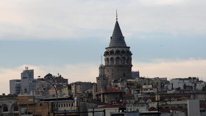 """FILE - In this May 10, 2011 file photo, one city's landmarks, Galata Tower is seen in Istanbul, Turkey.  On a moonlit night in the backstreets of Beyoglu, one of Istanbul's oldest districts, the worn facades and sharp-angled shadows recall the mournful character of the city that Nobel-prize winning Turkish author Orhan Pamuk described in a memoir. New, brash Istanbul charges ahead, and it's harder to uncover those pockets of dark ruin that epitomize """"huzun,"""" the dense, communal melancholy that permeated the former imperial capital in Pamuk's work. As Turkey strives for global status, its leading city strains to channel expansion that threatens its heritage, environment and even its identity. (AP Photo/Burhan Ozbilici, File)"""