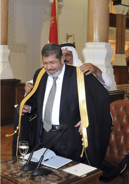 Egypt's President-elect Mohamed Mursi receives an abaya from an unknown member of Sini Party during a meeting with Egyptian party leaders at the presidential palace in Cairo