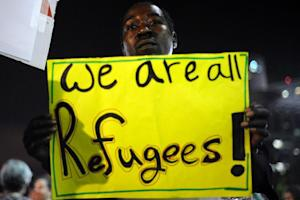 An African migrant holds a sign during a demonstration …