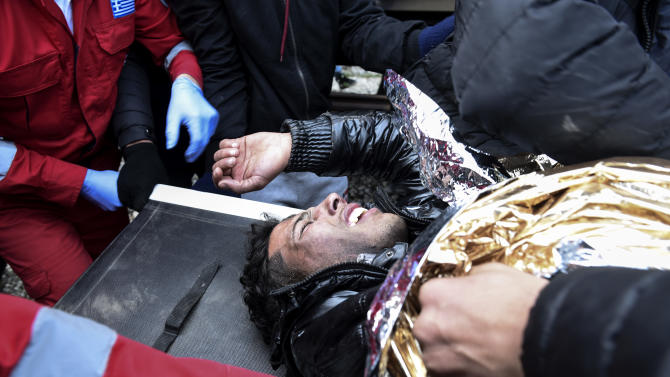 A man who has been electrocuted is treated by others at the Greek-Macedonian border, near the northern Greek village of Idomeni, on Saturday, Nov. 28, 2015.  Tension has flared on the Greek side of the Greece-Macedonia border when a migrant who was stopped from crossing into Macedonia, suffered severe burns when he climbed on top of a stationary train carriage and touched a overhead power cable.  (AP Photo/Giannis Papanikos)