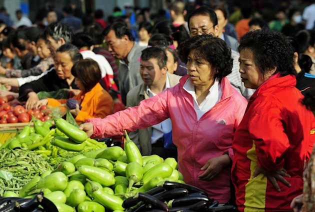 A woman buys fresh vegetables at a market in Shenyang in northeast China's Liaoning province, Thursday May 10, 2012. China's inflation rate slowed slightly to 3.4 percent in April, down from 3.6 percent a month earlier, giving the government greater leeway to ease policy to boost the economy. (AP Photo) CHINA OUT