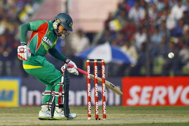 Bangladesh's Mushfiqur Rahim reacts in pain after he was hit by a ball during the Asia Cup one-day international cricket tournament against India in Fatullah, near Dhaka, Bangladesh, Wednesday, Fe