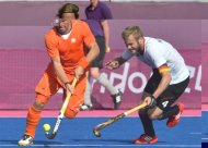 Roderick Weusthof (L) of Netherlands dribbles past Maximilian Mueller (R) of Germany during the men's field hockey preliminary round match between The Netherlands and Germany at the Riverbank Arena in London during the London 2012 Olympic Games. The Netherlands team joined their women's counterparts as semi-finalists in the Olympic hockey tournament on Sunday by beating Germany 3-1