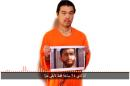 This still image taken from a video posted on YouTube by jihadists on Tuesday, Jan. 27, 2015, purports to show a still photo of Japanese journalist Kenji Goto holding what appears to be a photo of Jordanian pilot 1st Lt. Mu'ath al-Kaseasbeh. Both are being held hostage by the Islamic State militant group. The still image was overdubbed with audio which condemns Jordan for not releasing Sajida al-Rishawi, saying that unless she is freed within 24 hours both will be killed. (AP Photo)