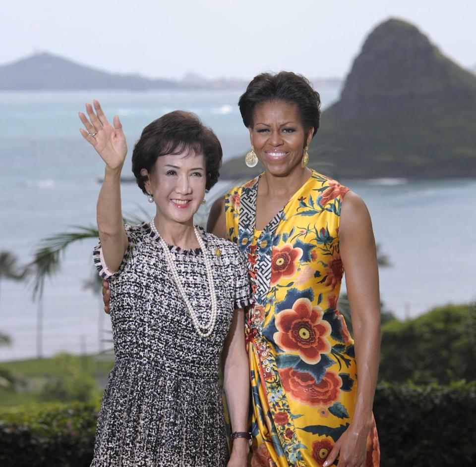 First lady Michelle Obama greets Fang-Yui Lien, spouse of the Representative of Chinese Taipei, before the APEC Spousal Luncheon at Kualoa Ranch in Ka'a'awa, Hawaii, Sunday, Nov. 13, 2011. Mokolii Island is in the distance. (AP Photo/Susan Walsh)