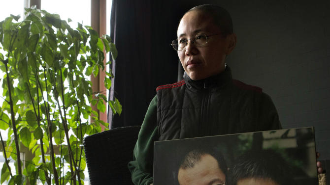 """FILE - In this Thursday, Dec. 6, 2012 file photo, Liu Xia, the wife of China's jailed Nobel Peace Prize winner Liu Xiaobo, poses with a photo of her and her husband during an interview at her home in Beijing. Liu Xia wrote an open letter to new Chinese leader Xi Jinping to protest an 11-year prison term given to her brother, the family's lawyer said Friday, June 14, 2013. In the letter, she said the sentencing was unfair and urged Xi to govern China in a way that respects the rights of individuals and avoids """"ruthless suppression based on violence."""" (AP Photo/Ng Han Guan, File)"""