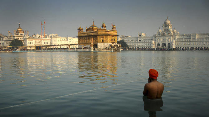 """FILE- In this Jan. 1, 2014 file photograph, an Indian Sikh devotee takes a holy dip in the sacred pond at the Golden Temple in Amritsar, India. The British government has admitted it advised India before the deadly 1984 raid on the Golden Temple in Amritsar.Foreign Secretary William Hague told Parliament on Tuesday, Feb. 4, 2014 that British military advice had only a """"limited impact"""" on the operation. (AP Photo/Sanjeev Syal,file)"""