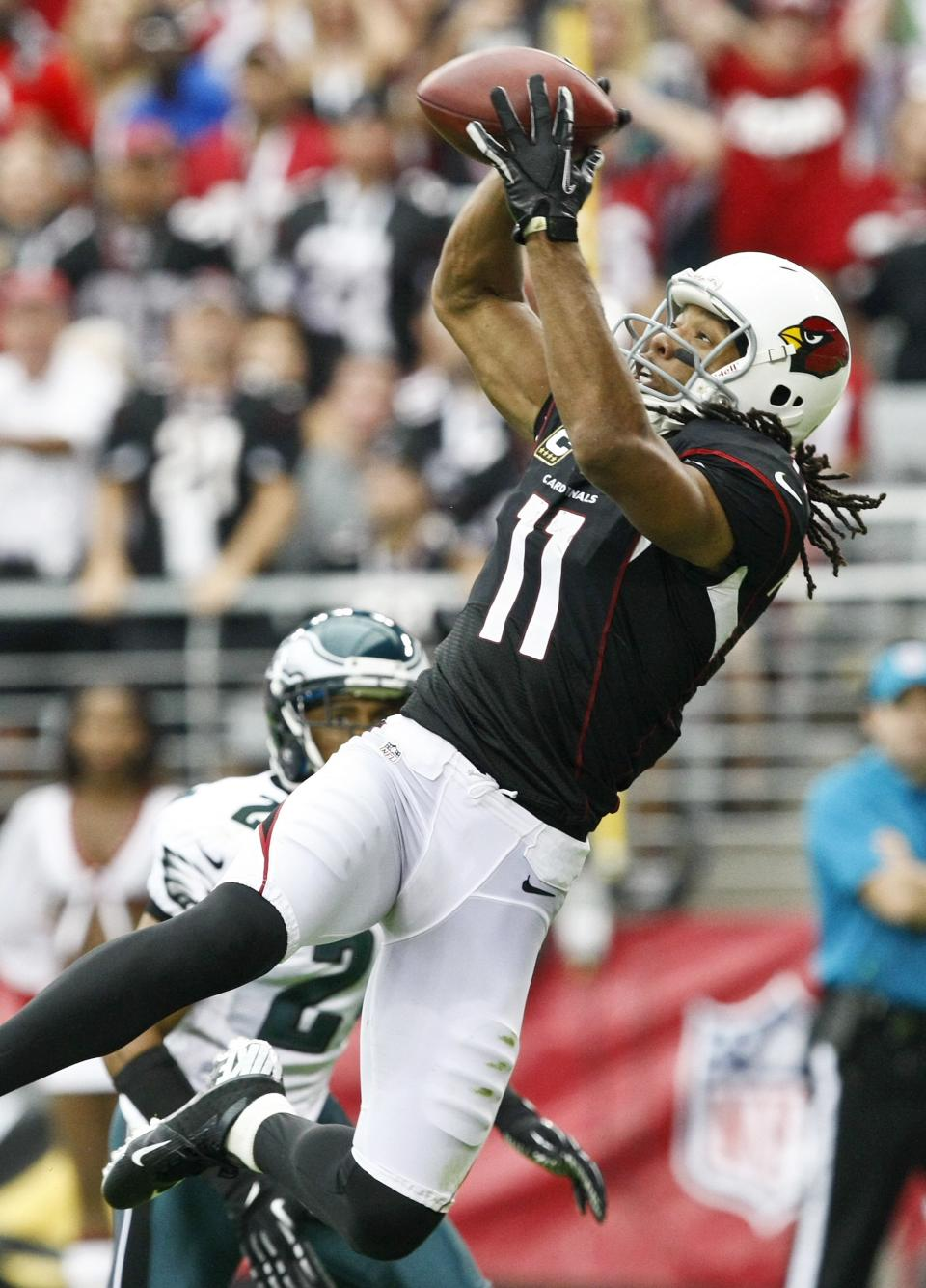 Arizona Cardinals' Larry Fitzgerald (11) makes a jumping touchdown catch in front of Philadelphia Eagles' Nnamdi Asomugha in the first half of an NFL football game on Sunday, Sept. 23, 2012, in Glendale, Ariz. (AP Photo/Rick Scuteri)