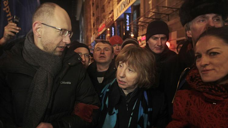 Ukrainian opposition leader Arseniy Yatsenyuk, left, and EU foreign policy chief Catherine Ashton, center, arrive to meet Pro-European Union activists gathered on the Independence Square in Kiev, Ukraine, Tuesday, Dec. 10, 2013. Some demonstrators arrested in the massive protests sweeping Ukraine's capital will be released, embattled President Viktor Yanukovych promised Tuesday, trying to defuse a political standoff that is threatening his leadership. (AP Photo/Sergei Chuzavkov)