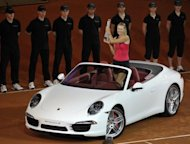 Russia's Maria Sharapova poses for photos with the winner's prize, a Porsche 911 Carrera, after defeating Victoria Azarenka of Belarus in the final of the WTA Porsche Tennis Grand Prix in Stuttgart, southwestern Germany, on April 29. Sharapova won 6-1, 6-4