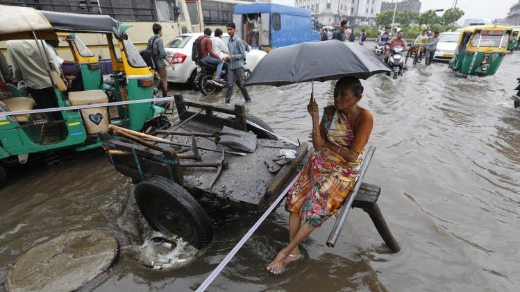 A municipal worker sits in cart next to a choked manhole on a flooded street after heavy rains in the western Indian city of Ahmedabad