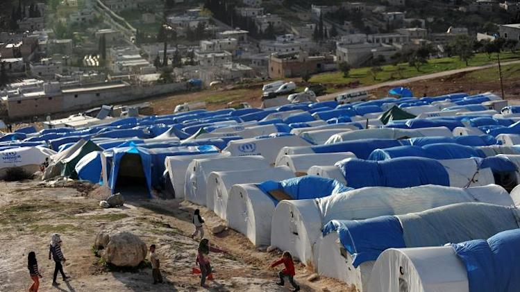 Syrian children play outside their makeshift houses at the refugee camp of Qah along the Turkish border in the village of Atme in the northwestern province of Idlib, on March 17, 2013