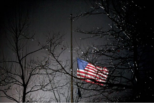 A U.S. flag flies at half staff outside the  Newtown High School before President Barack Obama is scheduled to attend a memorial for the victims of the Sandy Hook Elementary School shooting, Sunday, D