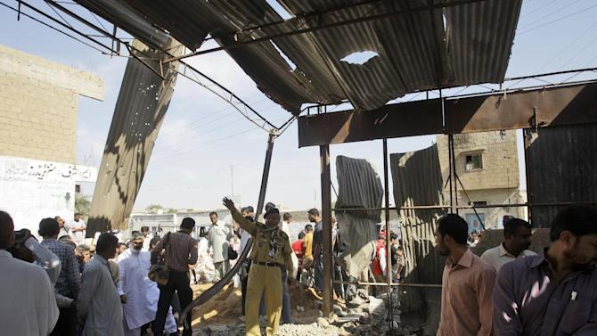 Pakistanis gather at the site of a bomb blast, in Karachi, Pakistan, Monday, Nov. 26, 2012. A bomb hidden in a cement construction block exploded in the southern city of Karachi killing at least one person and injuring several others, a police official said. (AP Photo/Shakil Adil)