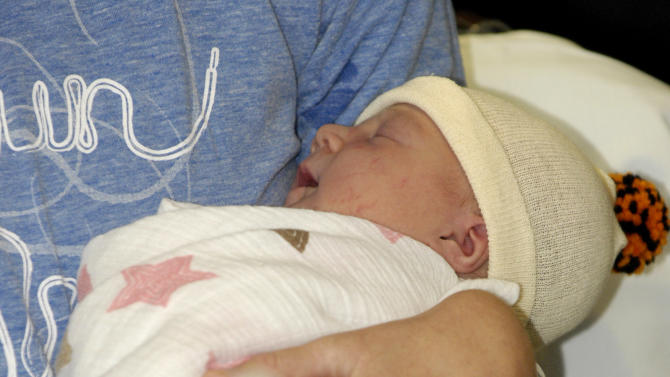 One-day-old June is held by her mother, Amber Miller, of Westchester, Ill.,  at Central DuPage Hospital in Winfield, Ill., Monday Oct. 10, 2011.  Miller felt contractions a few minutes after finishing the Chicago Marathon on Sunday and gave birth hours later to a baby daughter. (AP Photo/Daily Herald, Mark Black) MANDATORY CREDIT