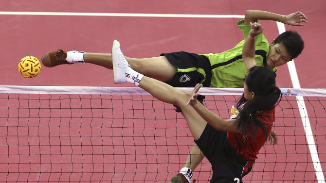 Myanmar's Phyu Phyu Than, top, kicks a ball as Laos player Koy Xayavong, front, blocks during the women's doubles sepak takraw final match at the 17th Asian Games Monday, Sept. 22, 2014 in Incheon, South Korea. (AP Photo/Eugene Hoshiko)