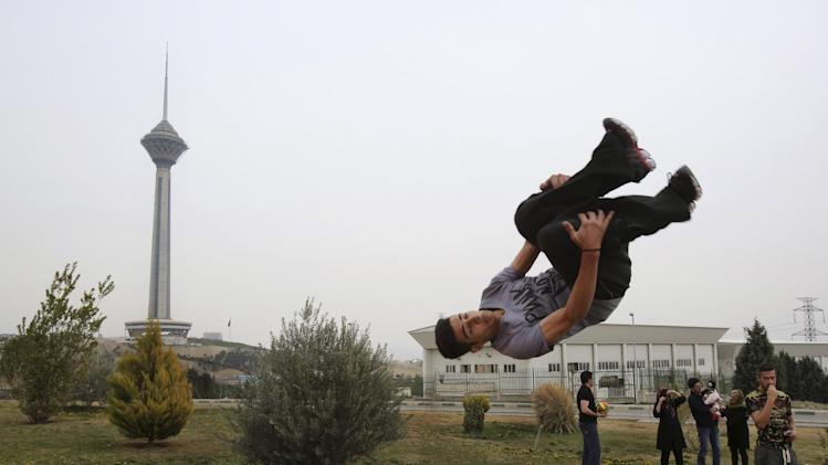 """Iranian Omid Khosravi practices parkour during the ancient festival of Sizdeh Bedar, an annual public picnic day on the 13th day of the Iranian new year, in Tehran, Iran, Wednesday, April 2, 2014. Sizdeh Bedar, which comes from the Farsi words for """"thirteen"""" and """"day out,"""" is a legacy from Iran's pre-Islamic past that hard-liners in the Islamic Republic never managed to erase from calendars. Many say it's bad luck to stay indoors for the holiday. (AP Photo/Vahid Salemi)"""