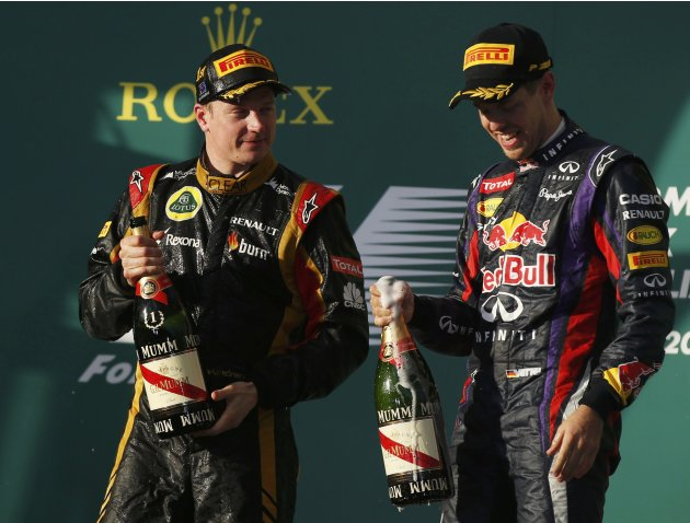 Lotus Formula One driver Kimi Raikkonen of Finland celebrates with Red Bull Formula One driver Sebastian Vettel of Germany after winning the Australian F1 Grand Prix in Melbourne
