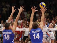 Serbia&#39;s Marko Podrascanin (L) and Ivan Milkovic are seen blocking a smash of Italy&#39;s Simone Parodi during a match in Vienna, in 2011. Eight men&#39;s volleyball teams, including Serbia, will fight it out for two of the remaining spots at the London Olympics in a round robin qualifying tournament starting in Japan on Friday